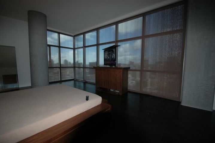 bedroom TV lift cabinet shown up against windows with a beautiful view