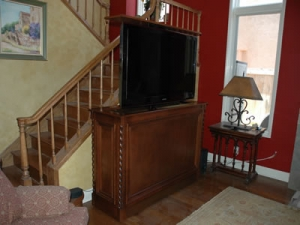 75 inch large TV raises by remote out of furniture against railing